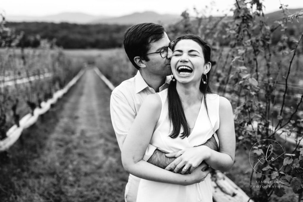 man and woman hugging and laughing during spring vineyard engagement session