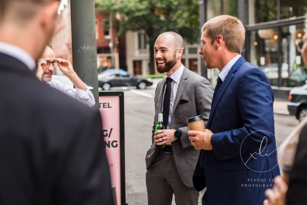 Groom chatting with friends and drinking at reception in Quirk Hotel