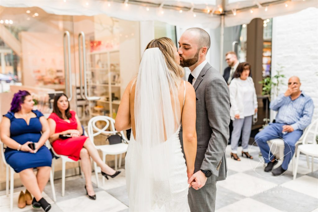Newly married couple kissing as husband and wife at wedding reception