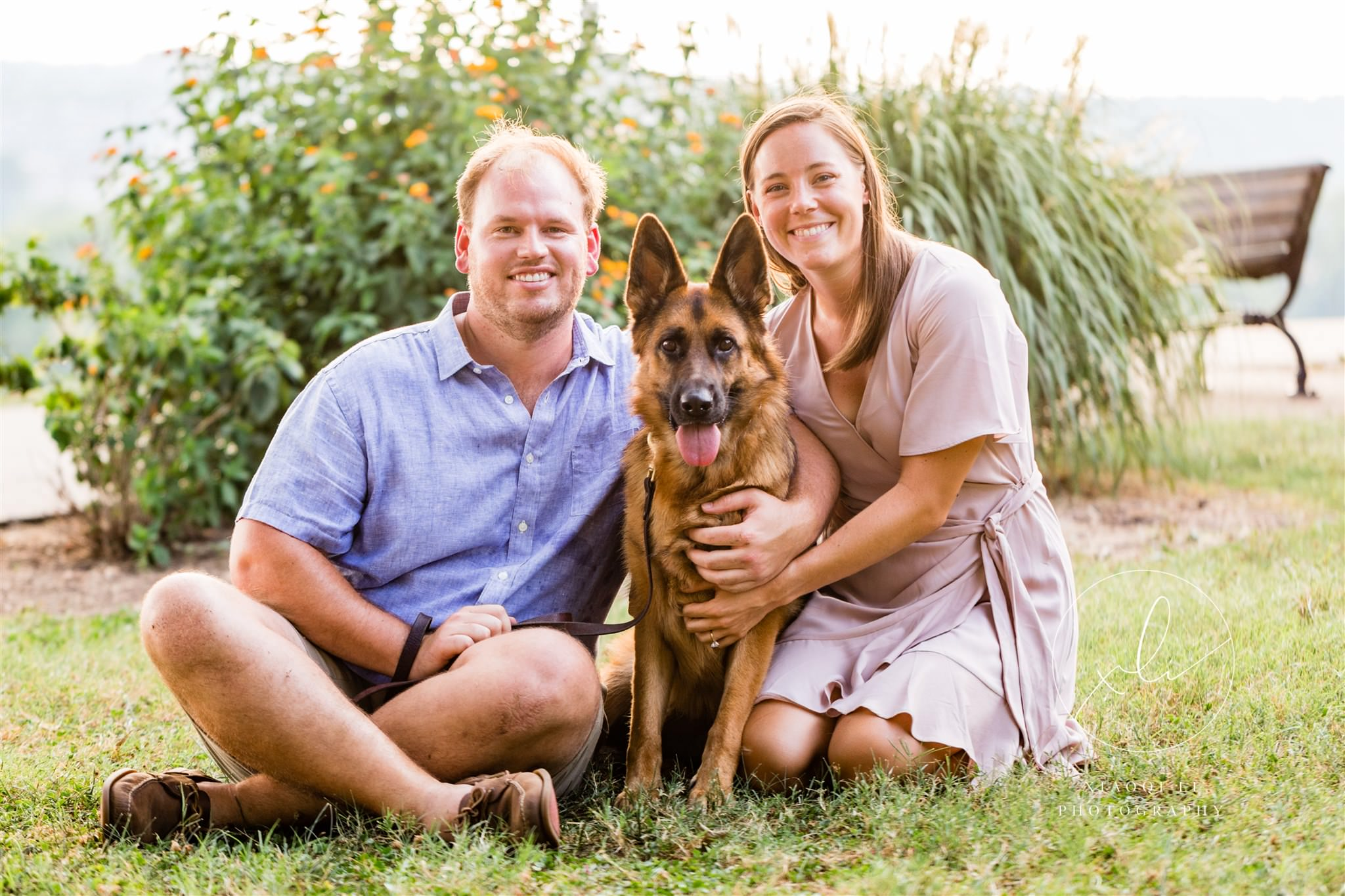 newly engaged couple sitting on ground with dog Stella during session