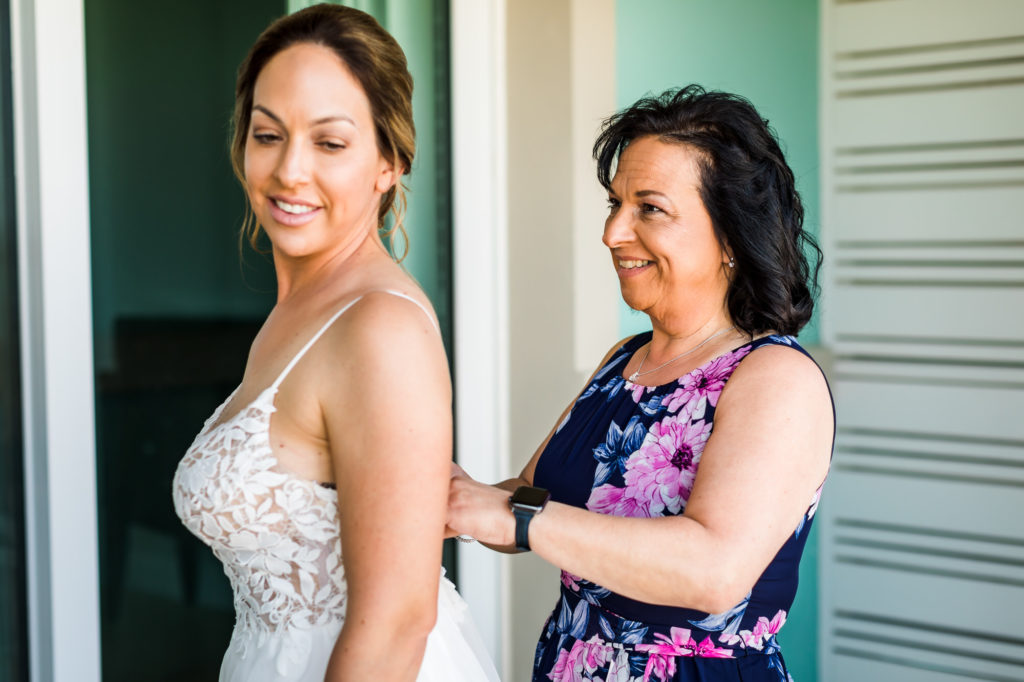 bride getting dresses buttoned up by family on wedding day