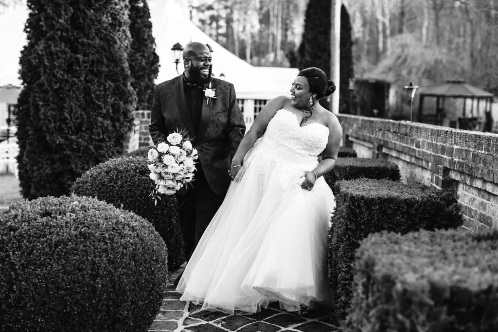 couple smiling and laughing as they walk through courtyard together just before becoming husband and wife