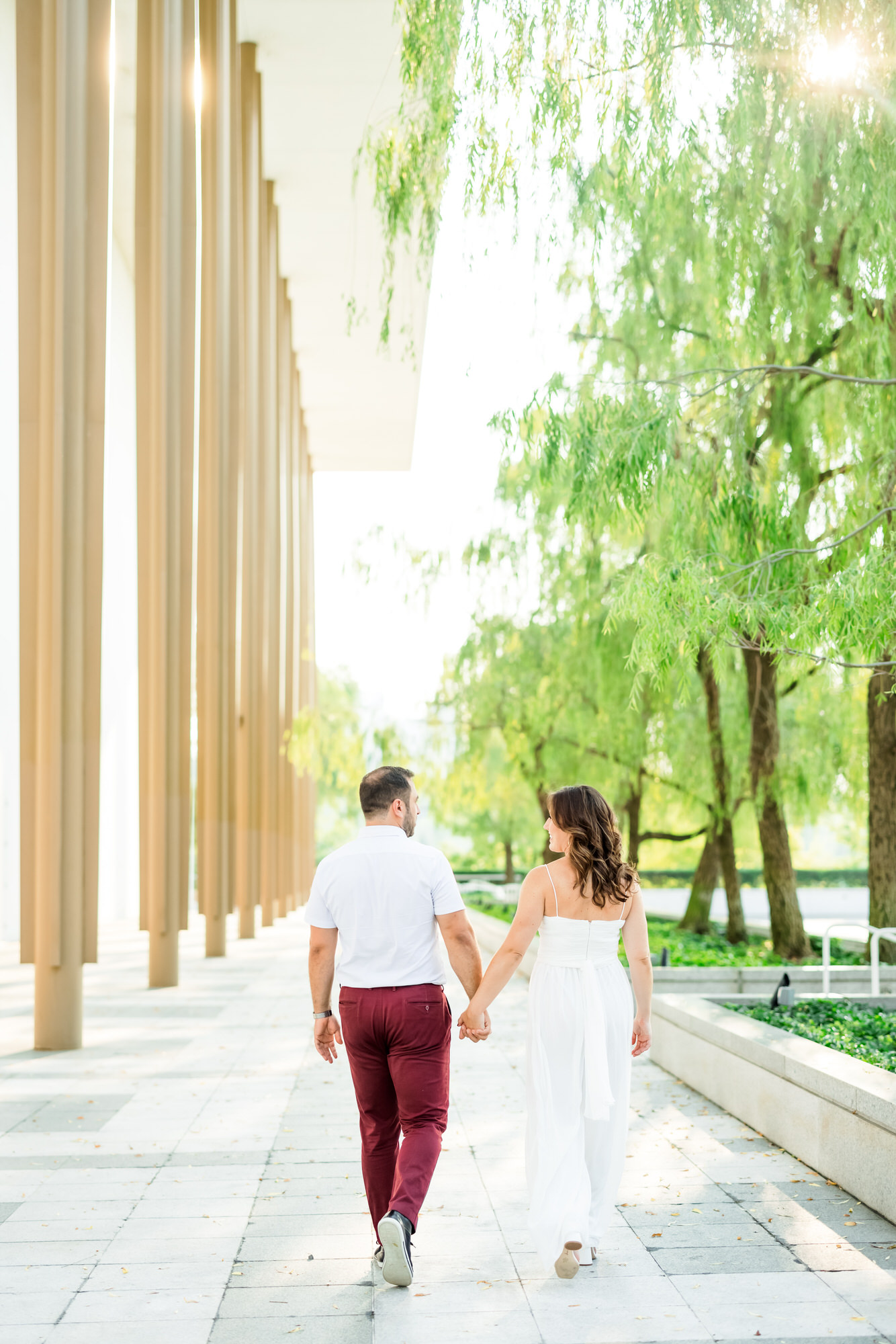 couple walking hand in hand during kennedy center engagement session