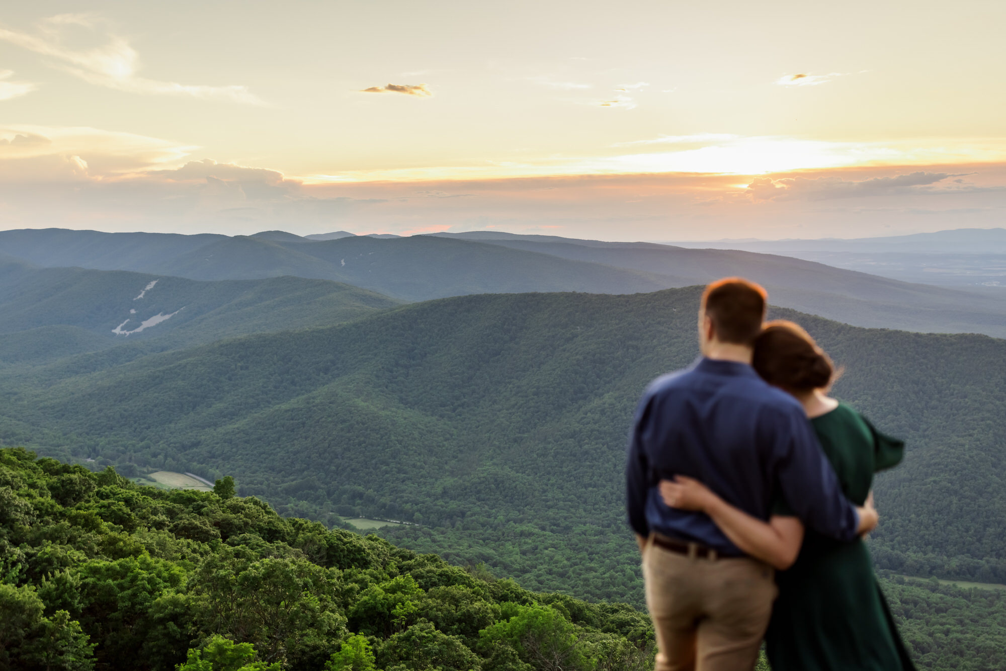 engaged couple looking over at the mountains during engagement session at Ravens Roost
