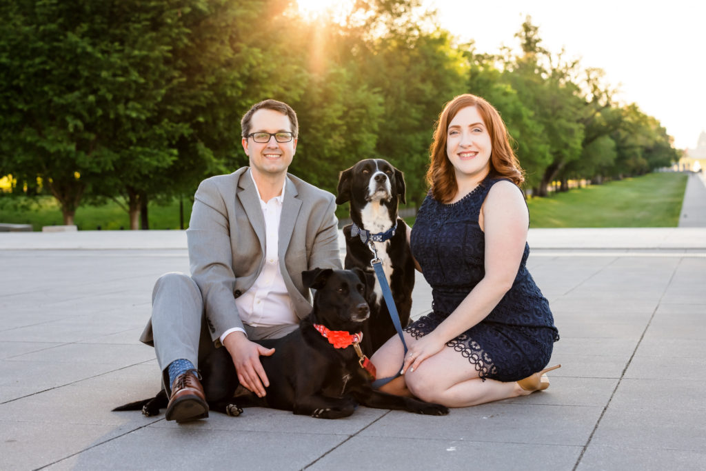 couple sitting with dogs during outdoor engagement session in DC